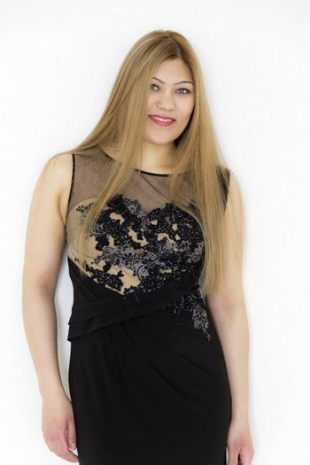 Attractive young girl with healthy straight hair in evening black long dress