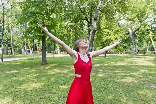Lady in red are standing with upwards hands at summer day