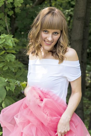 Young smiling woman in pink skirt on wood background