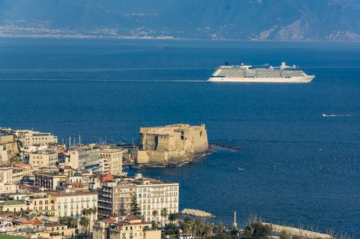 A cruise boat surf in the Bay of Naples with the the view of the castle, Italy
