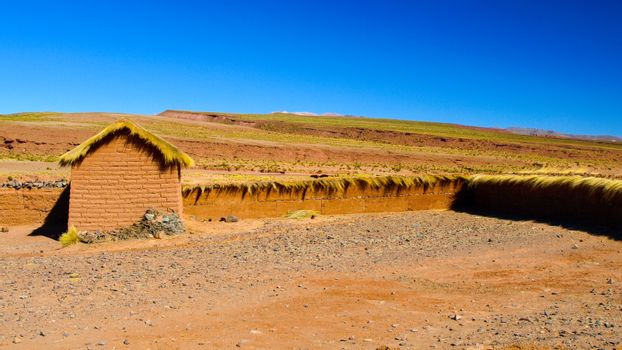 Landscape of southern Altiplano with clay brick wall and small hut, Andes, Bolivia