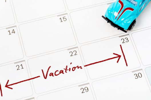 Vacation plan written on calendar with toy car.