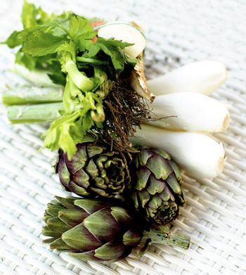 Ingredients of Artichoke Soup with Leek, Onion, Celery, Carrot, Garlic and Thyme closeup of Wicker background. Focus on Artichokes