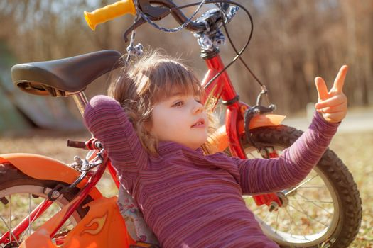 A young girl around four is leaning on a bike pointing forward.