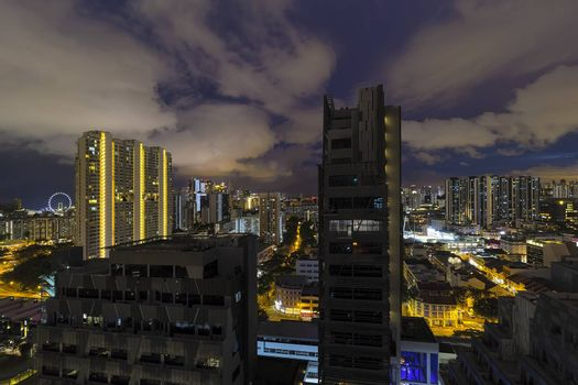 Singapore cityscape with rooftop view of apartment buildings with dramatic cloudy night sky