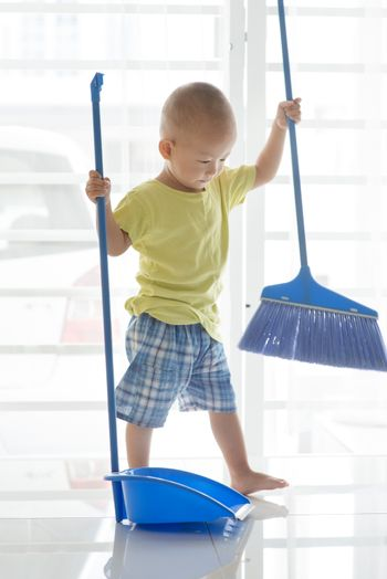 Asian baby boy sweeping floor with broom. Young child doing house chores at home.