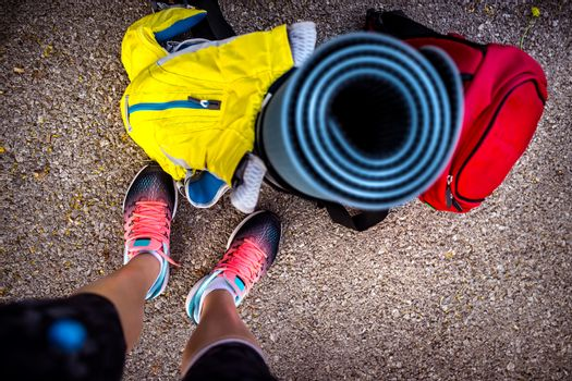 Conceptual photo of an active lifestyle, colorful sports gear on the floor, sportswoman prepares for workout, healthy life of young people