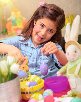 Cute girl decorate Easter eggs