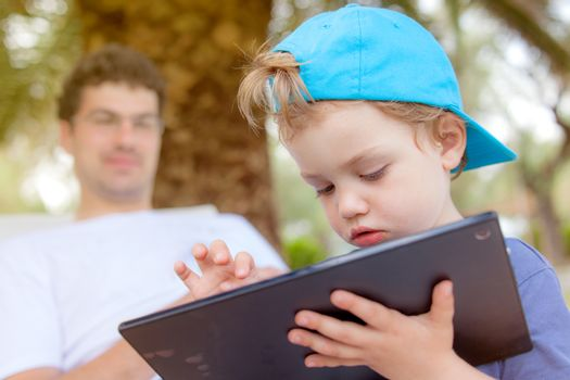 An infant child with food around his mouth is working, playing with tablet outdoors.