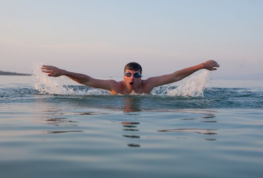 A male is swimming butterfly in the ocean or sea during sunset or sunrise.