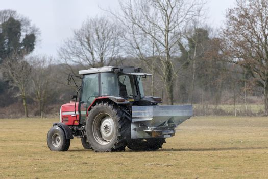Red tractor with automatic lime spreader that sprinkles on a meadow in the early spring in the hamlet called Achterhoek in the East of the Netherlands.