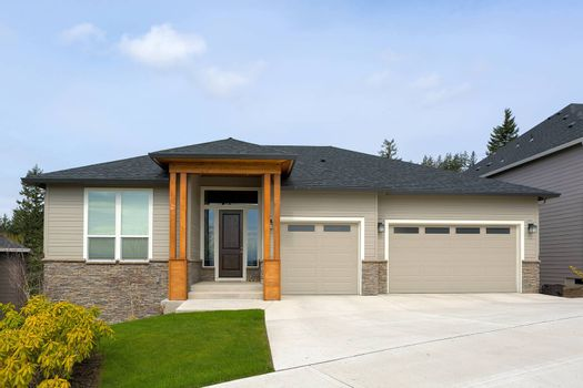 New custom built house in Happy Valley Oregon suburban neighborhood with three car garage and manicured front lawn