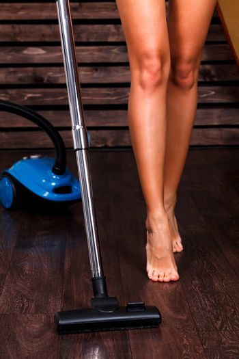 Long naked legs of woman cleaning the wooden floor with vacuum cleaner in the living room