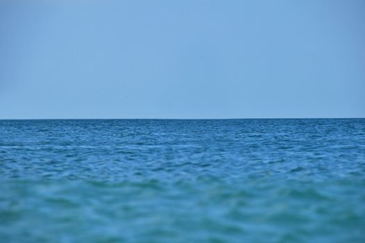 Tranquil scene of blue sea water, horizon and sky