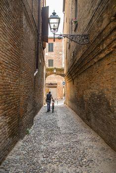 Ancient and narrow medieval street in Ferrara, Italy