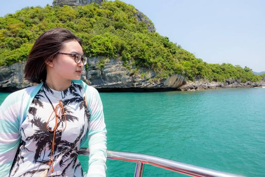 Teenage girl wear spectacles are traveling by boat to enjoy beautiful views of the sea and the island during the summer in Mu Ko Ang Thong National Park, Surat Thani province,Thailand