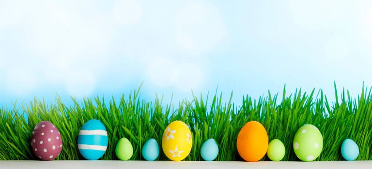 Row of Easter Eggs in fresh green grass over blue sky background