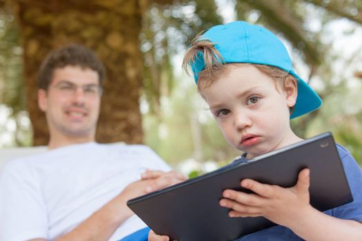 Little boy with dirty mouth is playing with his father tablet outdoors.