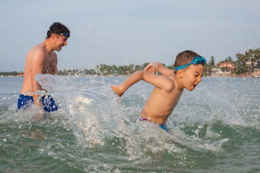 A boy around six is playing in the sea water with his father splashing.