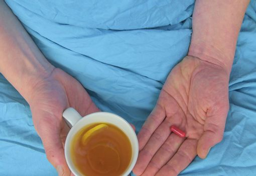 Ill man with fever drinking cup of warm tea and taking pill. Influenza season. Hands of the sick man holding pill and cup of the hot tea in the bed. Close-up of ill caucasian man at home.