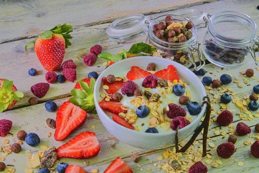 Composition of a typical genuine breakfast made with yogurt, blueberries, raspberries, blackberries, muesli. Concept of: fitness, diet, wellness and breakfasts