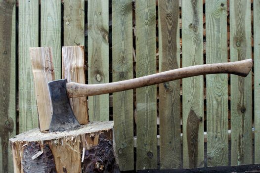 Old vintage axe stuck in wood log used to chop other wood logs.