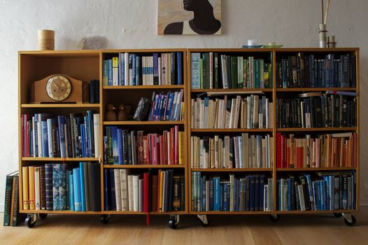 Wooden book shelf with many colorful books and a clock.