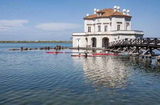 NAPLES - APRIL 7, 2012: royal hunting house on the Fusaro Lake with canoes under the bridge, on April 7, 2012 in Naples, Italy
