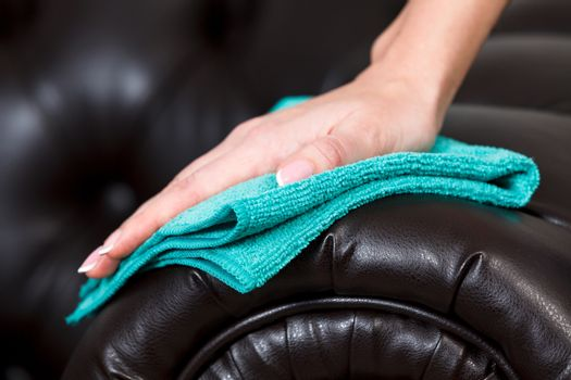Closeup shot of female hand with beautiful manicured fingers wiping brown leather couch