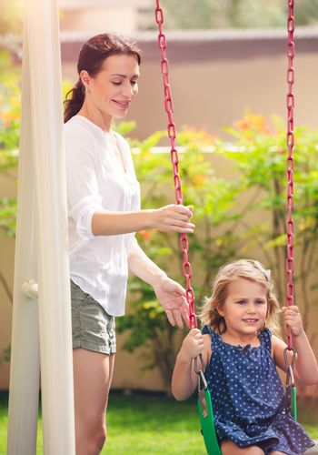 Mom rocks her daughter on a swing