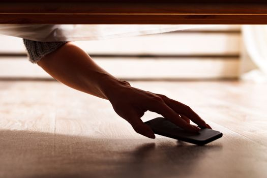 Someone is hiding a smartphone under the bed