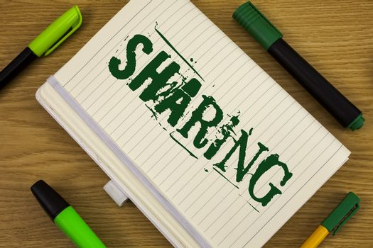 Text sign showing Sharing. Conceptual photo To Share Give a portion of something to another Possess in common written Notebook Book the wooden background Pen and Markers next to it.