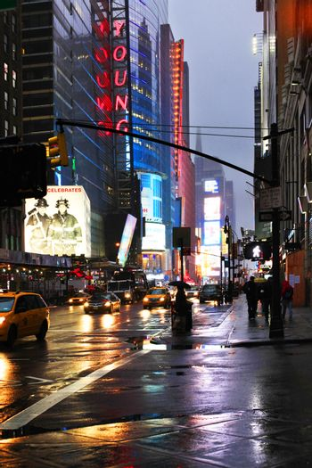 New York, USA - May 20, 2013: taxi's crossing at Time Square at night in the rain. The site is regarded as the world's most visited tourist attraction with nearly 40 million visitors annually.