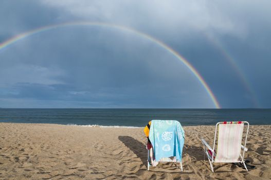 Chairs and rainbow on the beach in Maine, Usa