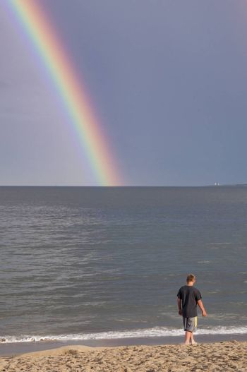 A young boy and rainbow on the beach in Maine, Usa