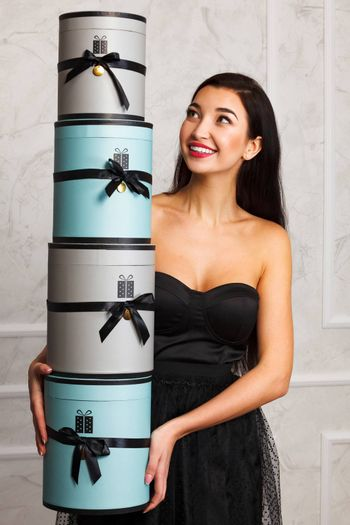 Smiling woman in black dress holds a pile of presents