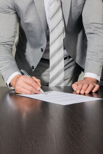 Businessman signing a contract standing near office desk