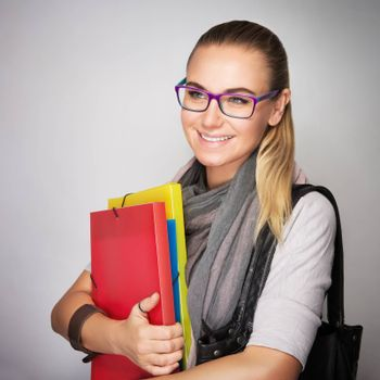 Happy student girl with colorful folders in hands isolated on gray background, enjoying start of school time, high education in the university