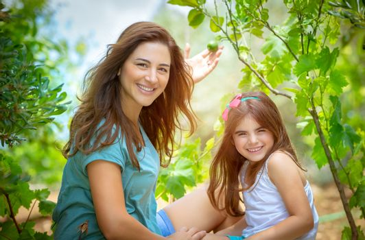 Mother with daughter in the orchard, enjoying the appearance of first fruits, young gardeners with pleasure spending time in the garden, happy life in countryside