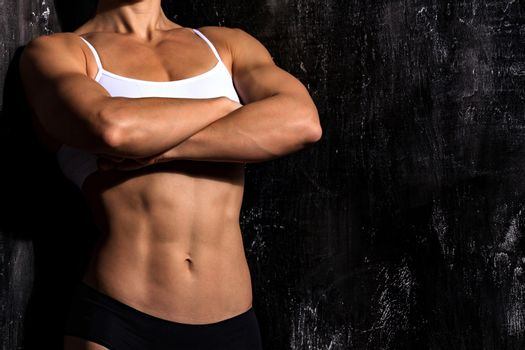 Muscular female torso wearing fitness clothing is posing against dark grunge background