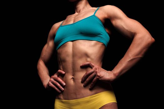 Fitness woman posing against a black background
