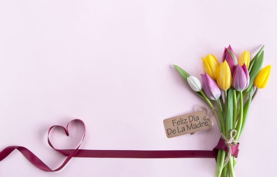 Heart shape ribbon attached to a bunch of flowers with label