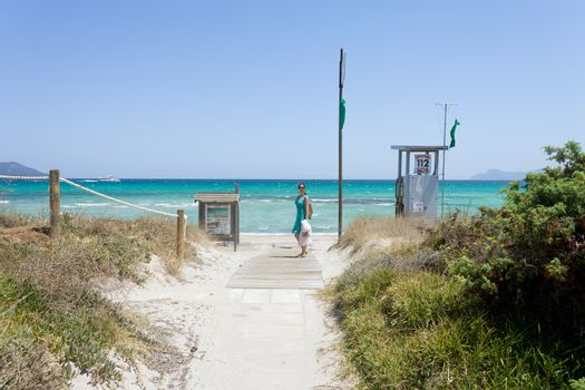 Platja de Muro, Mallorca - A woman walking to the lonely beach o