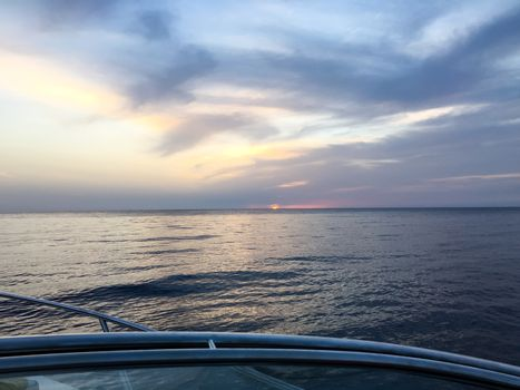 view from the boat to the sunset at the ocean at a trip