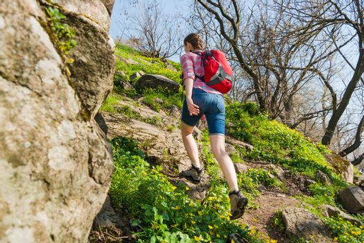 Young Couple Hiking with Backpacks on the Beautiful Rocky Trail at Sunny Evening. Family Travel and Adventure.