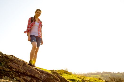Portrait of Happy Woman Traveler with Backpack Standing on the Rock at Sunny Evening. Travel and Adventure Concept.