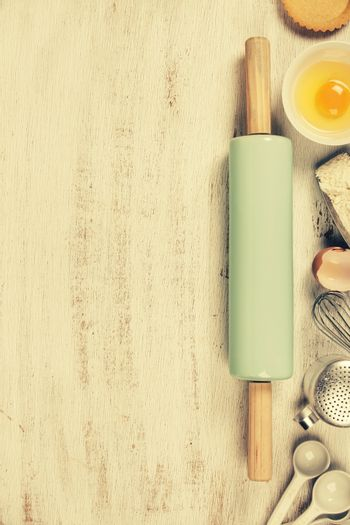 Baking tools and ingredients - flour, rolling pin, eggs, measuring spoons on vintage wood table. Top view. Rustic background with free text space