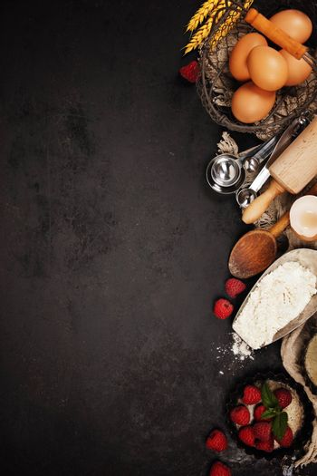 Baking tools and ingredients - flour, eggs, rolling pin, measuring spoons  on vintage table. Top view. Rustic background with free text space