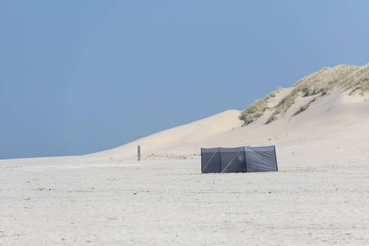 Wind screen on the beach with dunes on the background
