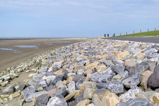 Wadden Sea dike with large colorful natural stone pebbles and cycle path from the island Ameland in northern Netherlands bordering the UNESCO protected Wadden Sea
